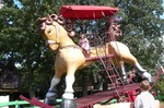 Samantha is riding Piccolo, the World's Largest Rocking Horse.